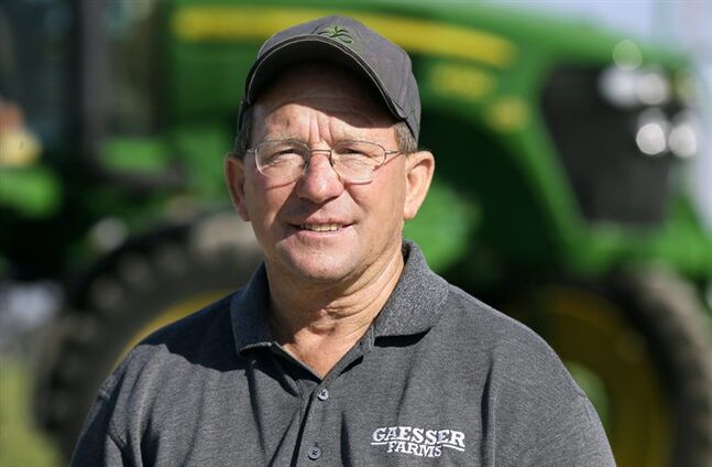 Ray Gaesser stands in front of a sprayer on his farm, Wednesday, June 11, 2014, near Corning, Iowa. U.S. companies relying on farmers for the raw materials in their products must take a more active role in ensuring the crops are grown in a way that minimizes damage to water, soil, and environment, a new report released Wednesday said. Gaesser, who farms 6,000 acres of corn and soybeans, said most farmers are willing to adopt new measures if they are shown to be beneficial to the land and water and do not reduce productivity. (AP Photo/Charlie Neibergall)