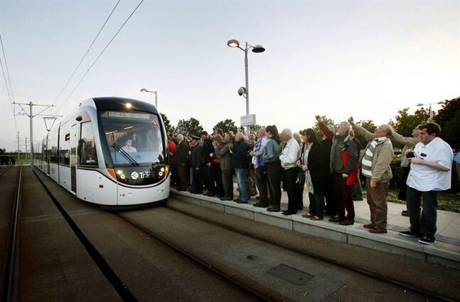Passengers wait to board a tram at the Gyle shopping center stop in Edinburgh, Scotland, Saturday, May 31, 2014. A state-of-the art tram system carried its first paying passengers through Edinburgh on Saturday - three years late and vastly over-budget. (AP Photo/PA, Danny Lawson) UNITED KINGDOM OUT, NO SALES, NO ARCHIVE