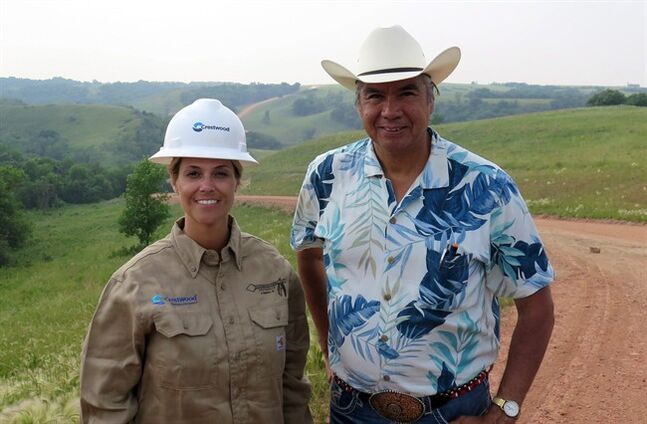 Miranda Jones, vice president of environmental safety and regulatory at Crestwood Midstream Partners, and Tex Hall, chairman of the Three Affiliated Tribes, pose for a photo near the site of a pipeline spill near Mandaree, N.D., Wednesday, July 9, 2014. A pipeline owned by a Crestwood subsidiary leaked around 1 million gallons of saltwater. Some of that liquid entered a bay that leads to a lake that is used for drinking water by the Three Affiliated Tribes. (AP Photo/Josh Wood)