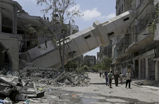 Palestinians walk under the fallen minaret of the Al-Sousi mosque that was destroyed in an Israeli strike at Shati refugee camp in Gaza City in the northern Gaza Strip on Friday, Aug. 22, 2014. (AP Photo/Adel Hana)