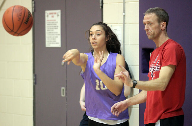 Vincent Massey basketball coach Brett Nohr, right, works with Zaina Bird during the Vikings varsity girls basketball practice at Massey on Wednesday. The Vikings varsity girls and varsity boys teams both begin the provincial AAAA high school championships as underdogs today in Winnipeg.