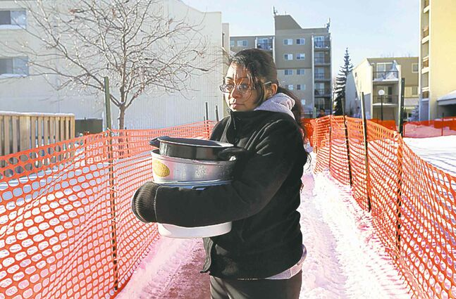 Vanessa Singh walks back to her apartment with large pots that she filled with boiling water and poured on her tires to try to free her car from the icy parking lot.