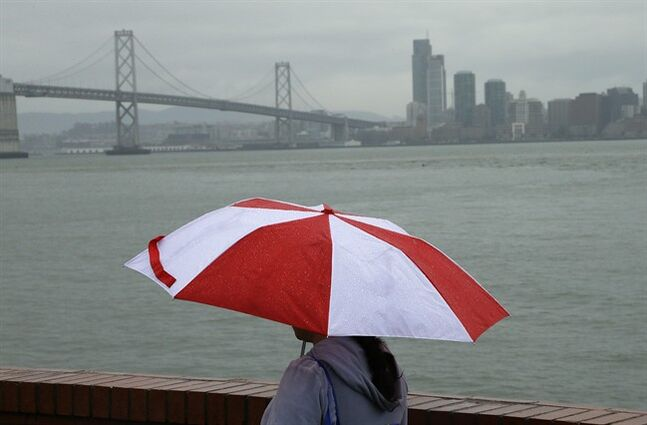 A women walks along Treasure Island with the San Francisco Bay bridge in the background during a rain storm Wednesday, Feb. 26, 2014, in San Francisco. Several winter storms are expected to bring rain to the Bay Area through the end of the week. (AP Photo/Ben Margot)
