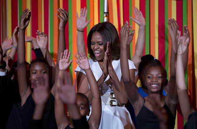 First lady Michelle Obama dances on stage with student performers as she and the President's Committee on the Arts and the Humanities (PCAH) host the White House Talent Show in the East Room of the White House, in Washington, Tuesday, May 20, 2014 in Washington. (AP Photo/Carolyn Kaster)