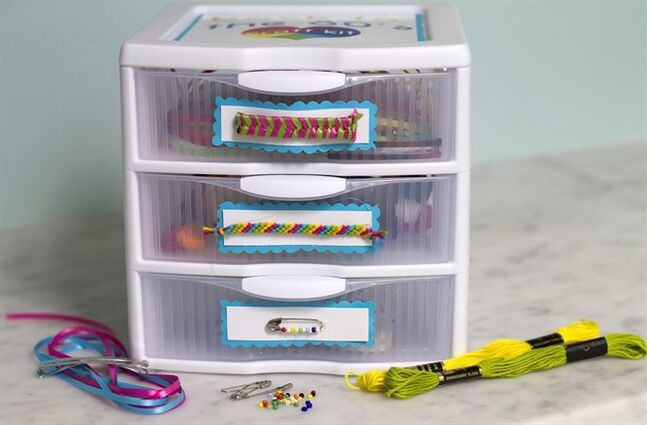 This Aug. 17, 2014, photo taken in Concord, N.H. shows a kit filled with supplies to make girly accessories from the 1980's: ribbon barrettes, friendship bracelets and friendship pins. (AP Photo/Holly Ramer)