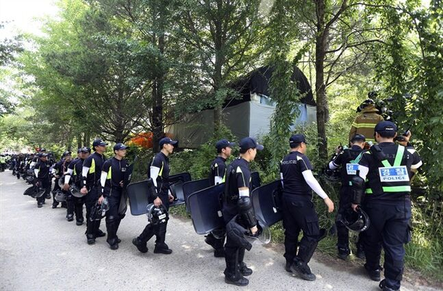 Police officers raid into a religious facility of the Evangelical Baptist Church in Anseong, South Korea, Thursday, June 12, 2014. Several thousand police officers, 6,000 on Wednesday and another 3,000 on Thursday, were mobilized to raid the sprawling South Korean church compound near Seoul to hunt for Yoo Byung-eun, a fugitive billionaire businessman and member of the church wanted in relation to the deadly ferry sinking in April. (AP Photo/Yonhap, Suh Myong-geun) KOREA OUT
