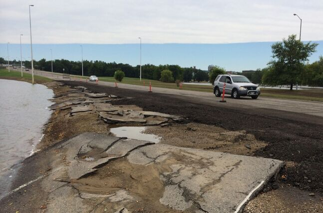 Some of the first traffic flows past damaged asphalt over the re-opened First Street North on Thursday afternoon. One lane in each direction has been opened to travel, some 20 days after it slipped under the waves of the rising Assiniboine River.