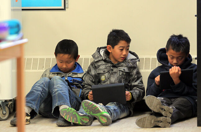 In this October 2012 photo, a trio of friends use iPads in their classroom at King George School. The Brandon School Division will continue rolling out its personalized learning with a focus on technology plan at four schools, including Alexander and Valleyview, this fall.