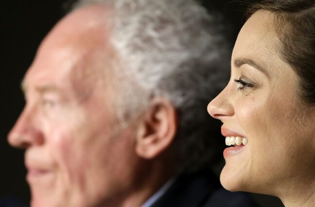 Actress Marion Cotillard, right, laughs during a press conference for Two Days, One Night (Deux jours, une nuit) as she sits alongside director Jean-Pierre Dardenne, left, at the 67th international film festival, Cannes, southern France, Tuesday, May 20, 2014. (AP Photo/Thibault Camus)