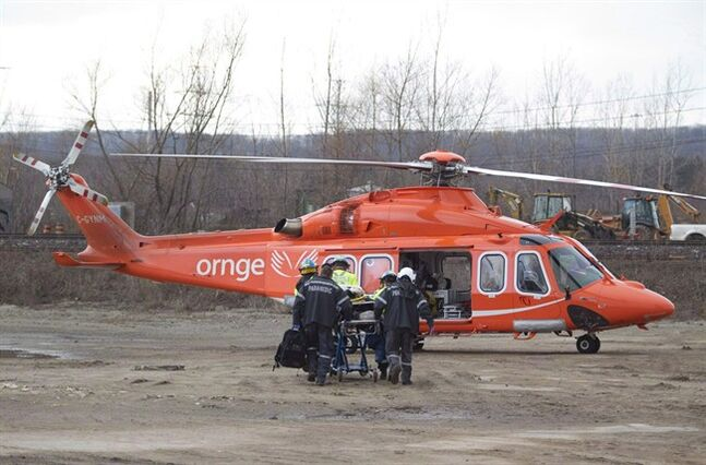Paramedics carry a patient to a Ornge helicopter in Burlington, Ont., February 26, 2012. THE CANADIAN PRESS/Pawel Dwulit