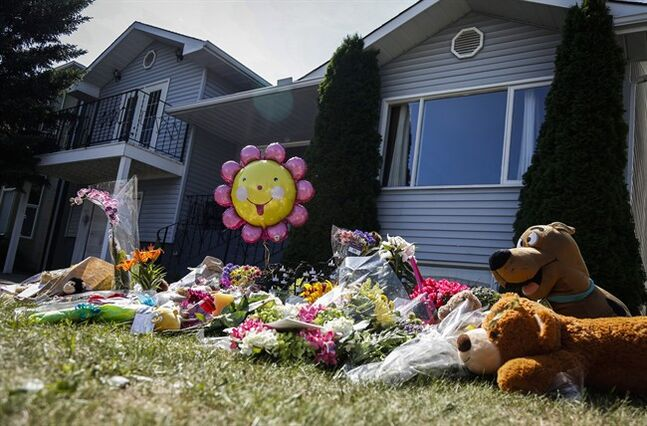Flowers and teddy bears are shown at an impromptu memorial for Nathan O'Brien and his grandparents, Alvin and Kathryn Liknes, at the Liknes home in Calgary, Alta., Tuesday, July 15, 2014. A man who has been under investigation in the disappearance of a Calgary boy and his grandparents has been formally charged with their murders. THE CANADIAN PRESS/Jeff McIntosh