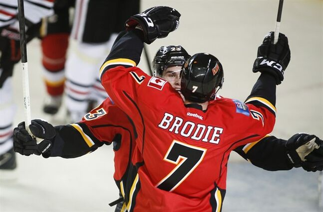 Calgary Flames' TJ Brodie, right, celebrates his game-wining goal with teammate Sean Monahan during overtime NHL hockey action in Calgary, Tuesday, Jan. 28, 2014. THE CANADIAN PRESS/Jeff McIntosh