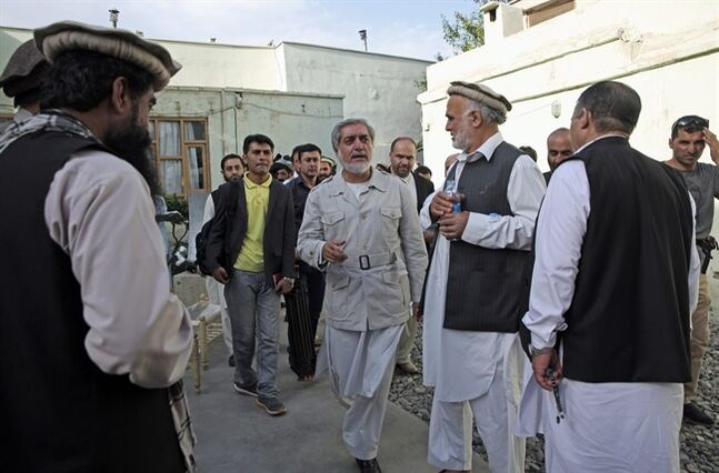 Afghanistan's presidential candidate Abdullah Abdullah, center, leaves a news conference in Kabul, Afghanistan, Thursday, June 19, 2014. Afghanistan's political crisis is showing no signs of easing as presidential candidate Abdullah said the electoral commission has ignored his demands and he will not resume cooperation with them.