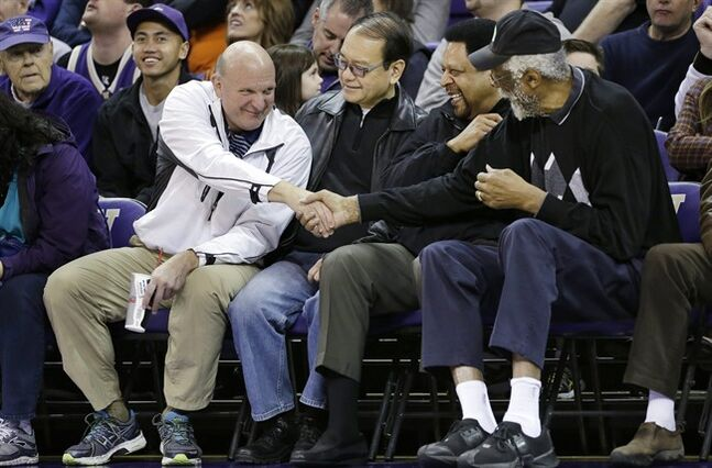 FILE - In this Jan. 25, 2014, photo, then-Microsoft CEO Steve Ballmer, left, shakes hands with former NBA players Bill Russell, right, and