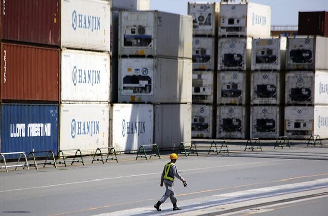 A port worker walks past a piles of cargo at a container terminal in Tokyo, Wednesday, Aug. 20, 2014. Japan's trade deficit rose in July from the month before to a wider than expected 964 billion yen ($9.4 billion), though exports were higher for the first time in three months, the government said Wednesday. (AP Photo/Eugene Hoshiko)