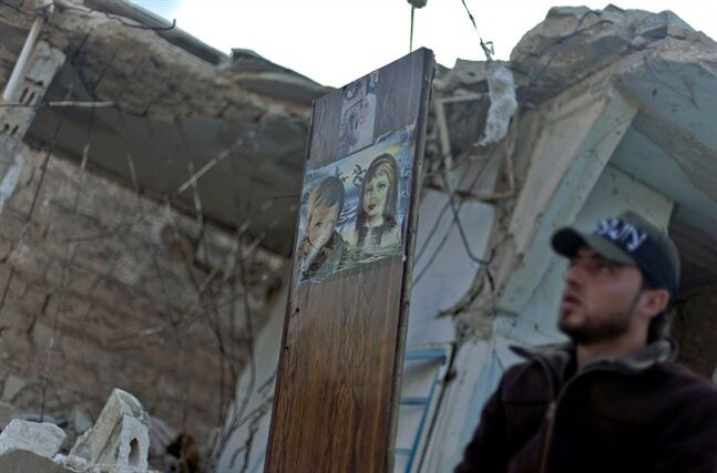 FILE - In this Friday, Nov. 16, 2012 file photo, A Free Syrian Army fighter stands next to a painting on a piece of wood left in a destroyed house in the town of Taftanaz, on the outskirts of Idlib, Syria. Syria's uprising was not destined to be quick. Instead, the largely peaceful protest movement that spread across the nation slowly turned into an armed insurgency and eventually a full-blown civil war. More than 130,000 people have been killed, and more than 2 million more have fled the country. Nearly three years after the crisis began, Syria's government and opposition are set to meet in Geneva this week for the first direct talks aimed at ending the conflict. (AP Photo/Khalil Hamra, File)