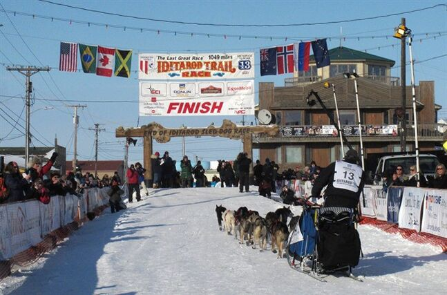 File - In this March 13, 2013 file photo, residents greet Kotzebue musher John Baker as he nears the finish line in Nome, Alaska. The Iditarod Trail Sled Dog Race will again have a national presence after race organizers have signed a deal with the Sportsman Channel. The outdoor network and its affiliated websites and magazines will promote the race, and the channel will air specials about the world's longest sled dog race ahead of the March 1 start in Alaska. (AP Photo/Mark Thiessen, File)