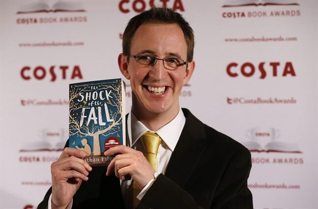 Costa Book of the Year shortlisted author Nathan Filer poses with his book The Shock of the Fall during the award ceremony in London, Tuesday, Jan. 28, 2014. (AP Photo/Sang Tan)