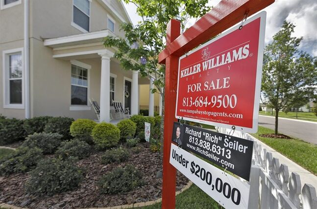 In this May 14, 2014 photo, a sign hangs in front of a new home for sale in Riverview, Fla. Freddie Mac reports on average U.S. mortgage rates for this week on Thursday, June 19, 2014. (AP Photo/Chris O'Meara)