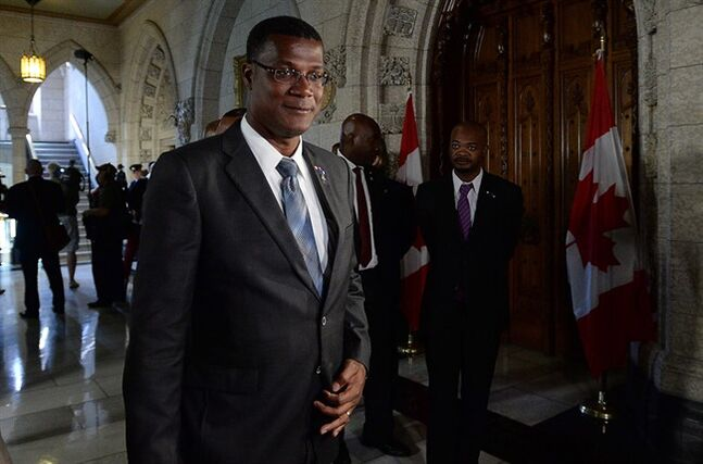 Rufus Ewing, Premier of the Turks and Caicos, leaves after holding a media availability in the Foyer of the House of Commons on Parliament Hill in Ottawa on Monday, May 26, 2014. THE CANADIAN PRESS/Sean Kilpatrick