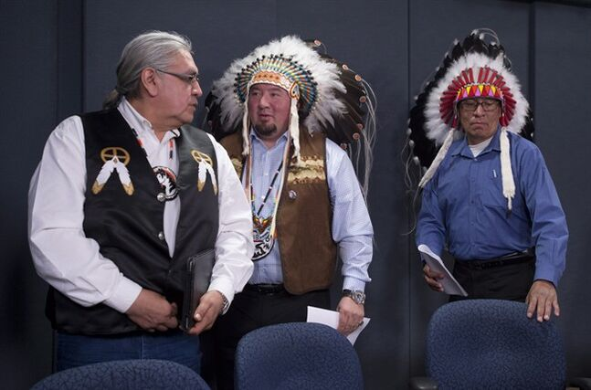 Grand Chief Derek Nepinak of the Assembly of Manitoba Chiefs (centre) speaks with Okimaw Wallace Fox (Onion Lake Cree Nation) (left) and Chief Craig Makinaw (Ermineskin Cree Nation) as they leave a press conference in Ottawa on Monday, April 28, 2014. The Chiefs discussed their rejection of Canada's Bill C-33, the