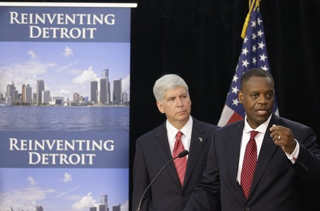 FILE - In this July 19, 2013, file photo, state-appointed emergency manager Kevyn Orr, right, and Michigan Gov. Rick Snyder, address reporters during a news conference in Detroit after Orr asked a federal judge for bankruptcy protection. Orr chose bankruptcy over diverting money from police, fire and other services to make debt payments. The move conserves cash so the city can operate, but it will hurt Detroit's image for years. It will also leave creditors with much less than they are owed and places in jeopardy the pension benefits of thousands of city retirees. (AP Photo/Carlos Osorio, File)