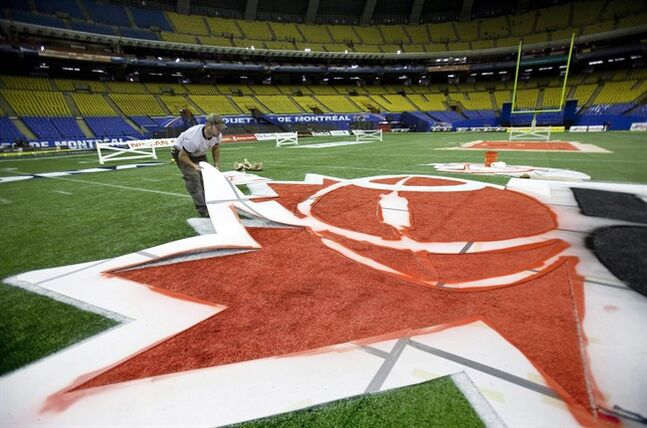 A worker paints a CFL logo in Montreal on November 20, 2010. THE CANADIAN PRESS/Paul Chiasson