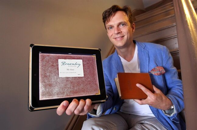 Software developer Andrew Burke, the creator of Remembary, a personal diary app, holds up a tablet at his home in Halifax, Tuesday July 22, 2014. Burke has kept a journal since 2003, and created the app in 2010. THE CANADIAN PRESS/Tim Krochak