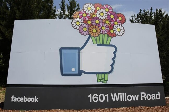 FILE - In this Sunday, May 13, 2012, file photo, flowers are added to a Facebook sign in front of Facebook headquarters in Menlo Park, Calif. (AP Photo/Paul Sakuma, File)