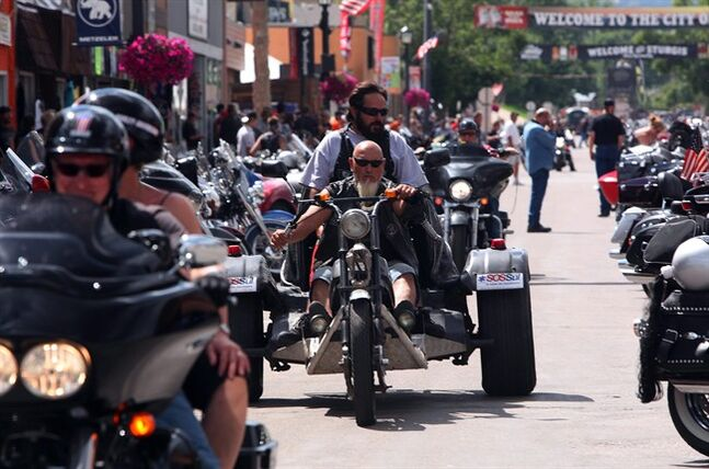 Bikers roar down Main Street during the 74th Annual Sturgis Motorcycle Rally in Sturgis, S.D, on Friday afternoon, August 1, 2014. Organizers expect attendance at this week's Sturgis Motorcycle Rally to top the estimated 466,000 who made the annual trek last year. (AP Photo/Toby Brusseau)