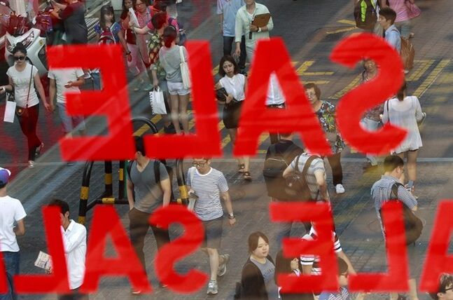 People walk on a shopping street in Seoul, South Korea, Thursday, July 10, 2014. South Korea's central bank said economic growth will be slower than expected this year because consumer spending has waned following a deadly ferry sinking. (AP Photo/Ahn Young-joon)