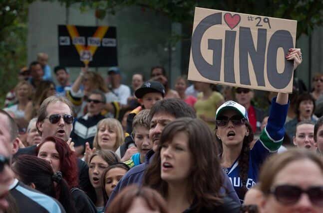 A woman cheers and holds a sign as hundreds of fans gather in support of Vancouver Canucks' enforcer Gino Odjick outside Vancouver General Hospital on Sunday June 29, 2014.