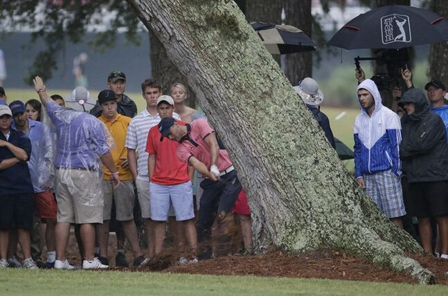 Martin Kaymer of Germany, hits from behind a tree off the 15th fairway during the final round of The Players championship golf tournament at TPC Sawgrass, Sunday, May 11, 2014 in Ponte Vedra Beach, Fla. Kaymer made double bogey on the hole but went on to win the championship. (AP Photo/John Raoux)