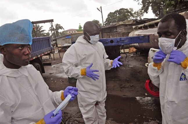 Liberian health worker prepare their Ebola protective gear before removing the body of a man that they believe died from the Ebola virus in Monrovia, Liberia, Friday, Aug. 29, 2014. The Ebola outbreak in West Africa eventually could exceed 20,000 cases, more than six times as many as are now known, the World Health Organization said Thursday. A new plan released by the U.N. health agency to stop Ebola also assumes that the actual number of cases in many hard-hit areas may be two to four times higher than currently reported.(AP Photo/Abbas Dulleh)