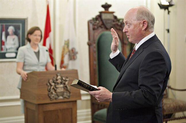 Alberta Premier Alison Redford watches as newly-appointed Minister of Energy Ken Hughes is sworn in during the swearing in of the new cabinet team at the Government House in Edmonton on May 8, 2012. One of two declared candidates in Alberta's Progressive Conservative race has dropped out to support former federal Conservative cabinet minister Jim Prentice. Former Municipal Affairs minister Ken Hughes says he entered the race in good faith and had planned to stay in it until a winner is declared in September. THE CANADIAN PRESS/Jason Franson