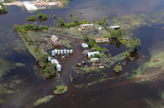 Floodwaters invade a farmstead near Gainsborough, Sask., during Saskatchewan Premier Brad Wall's aerial tour of flood-ravaged southeast Saskatchewan on Wednesday, July 02, 2014. THE CANADIAN PRESS/Don Healy - Pool