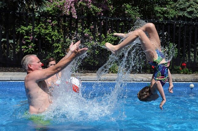 Stuart Lowther launches his daughter Brooke, 10, in their backyard pool in Burlington, Ont. as wife Deb Lowther looks on, Sunday, June 1, 2014. THE CANADIAN PRESS/Galit Rodan