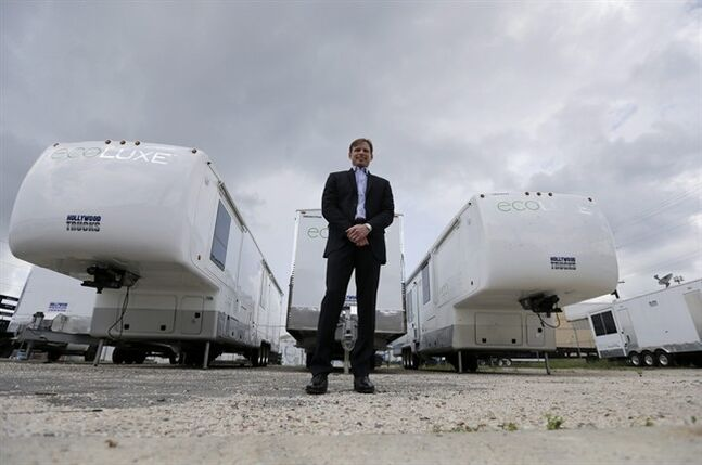 In this Tuesday, May 13, 2014 photo, Andre Champagne, owner of Hollywood Trucks, a fleet of top-end talent trailers servicing the movie industry in New Orleans, poses for a photo in front of some of his new eco-friendly trailers. Due to the growing number of films being filmed in Louisiana, Hollywood Trucks has grown annual revenue from about $600,000 in its first year in 2007 to $5 million in 2013, according to Champagne. The company recently expanded to Georgia and has plans to open in London. (AP Photo/Gerald Herbert)