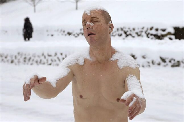 A statue of a man sleepwalking in his underpants is surrounded by snow on the campus of Wellesley College, in Wellesley, Mass., Wednesday, Feb. 5, 2014. The sculpture entitled