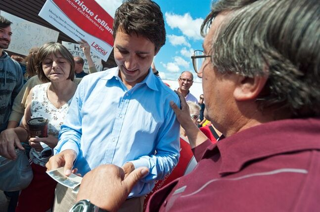 A man shares pictures withLiberal Leader Justin Trudeau during a campaign stop with New Brunswick Liberal Leader Brian Gallant in Moncton, N.B. on Saturday, August 23, 2014. THE CANADIAN PRESS/Marc Grandmaison