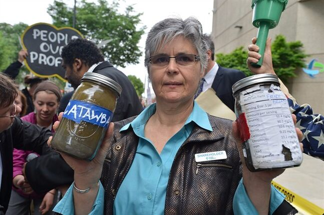 Duke Energy shareholder Donna Lisenby holds two jars of coals ash from the Catawba and French Broad rivers, as she demonstrates with other protesters Thursday, May 1, 2014, before going into the annual shareholders meeting in Charlotte, N.C. Some Duke Energy investors plan to push the utility's board of directors to investigate issues surrounding a massive coal ash spill that dumped toxic sludge into a 70-mile stretch of a North Carolina river. (AP Photo/The Charlotte Observer, T. Ortega Gaines) MAGS OUT; TV OUT; NEWSPAPER INTERNET ONLY (REV-SHARE)