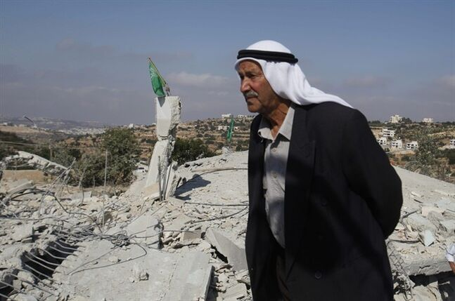 A Palestinian man stands near the rubble of the house of Hussam Kawasma, one of three Palestinians identified by Israel as suspects in the killing of three Israeli teenagers, after it was demolished by the Israeli army in the West Bank city of Hebron, Monday, Aug. 18 , 2014. Troops also demolished the home of another militant suspected in the abduction and killing of the teens, whose deaths sparked the war in Gaza, and sealed up the home of a third. (AP Photo/Nasser Shiyoukhi)