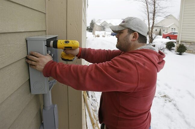 In this Friday, Jan. 10, 2014, photo, Paquale Cocca installs a new electrical box on a new home, in Pepper Pike, Ohio. The Commerce Department releases housing starts for January on Wednesday, Feb. 19, 2014. (AP Photo/Tony Dejak)