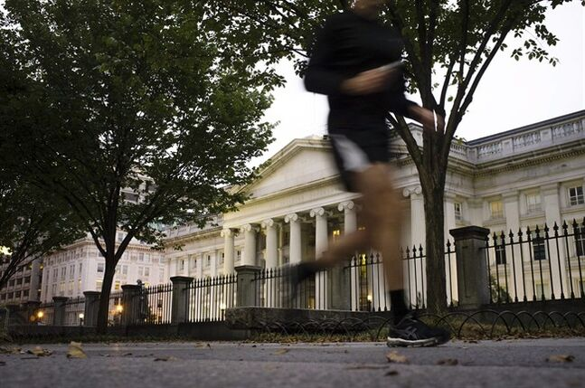 FILE - In this Oct. 16, 2013, file photo, a jogger on an early morning run passes the U.S Treasury Building in Washington. The Treasury Department releases budget data for July 2014 on Tuesday, Aug. 12, 2014. (AP Photo/J. David Ake, File)