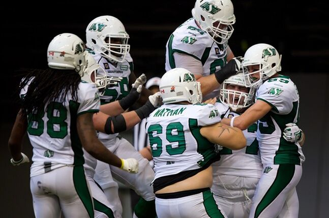 Saskatchewan Roughriders' Dan Clark, second right, is mobbed by his teammates as they celebrate his touchdown against the B.C. Lions during the second half of a CFL football game in Vancouver, B.C., on Sunday August 24, 2014. THE CANADIAN PRESS/Darryl Dyck