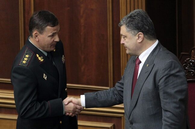 Ukrainian President Petro Poroshenko, right, congratulates new Ukrainian defense Minister Valeriy Heletey during a session of the parliament in Kiev, Ukraine, Thursday, July 3, 2014. Ukraine's president shook up the leadership of his poorly performing military on Thursday, appointing a new defense minister and top general tasked with stamping out the corruption that has left the country's armed forces faltering before a pro-Russian insurgency. (AP Photo/Sergei Chuzavkov)