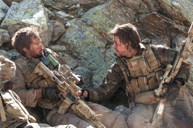 This file photo released by Universal Pictures shows Taylor Kitsch, left, as Michael Murphy and Mark Wahlberg as Marcus Luttrell in a scene from the film, '��Lone Survivor.
