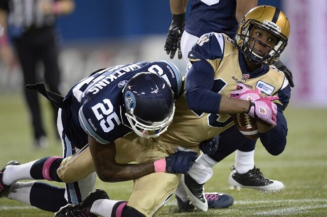 Winnipeg Blue Bombers' Aaron Kelly, 19, is stopped by Toronto Argonauts' Pat Watkins during first quarter CFL action in Toronto on Thursday Oct. 24, 2013. Kelly was signed by the Blue Bombers last year after the regular season was well under way. This year he says he's benefiting from a chance to attend training camp, learn the offence and become familiar with the team's quarterbacks.THE CANADIAN PRESS/Frank Gunn