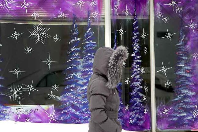 Dressed for winter, a pedestrian walks past a wintry scene painted on a downtown window earlier this month. Real snowflakes are expected tonight and intermittently through the weekend.