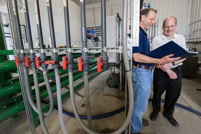 In this May 21, 2014 photo released by Michigan State University, Jim Wallace and Steven Safferman are shown at a dairy farm where they have helped to convert manure into clean water. THE CANADIAN PRESS/AP, Michigan State University, G.L Kohuth